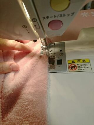 端を切ったフリースひざ掛けをミシンで縫い合わせる