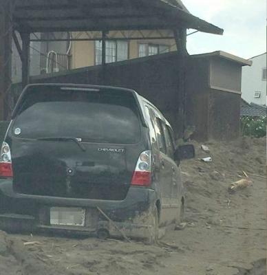 土砂に埋まり放置されている車