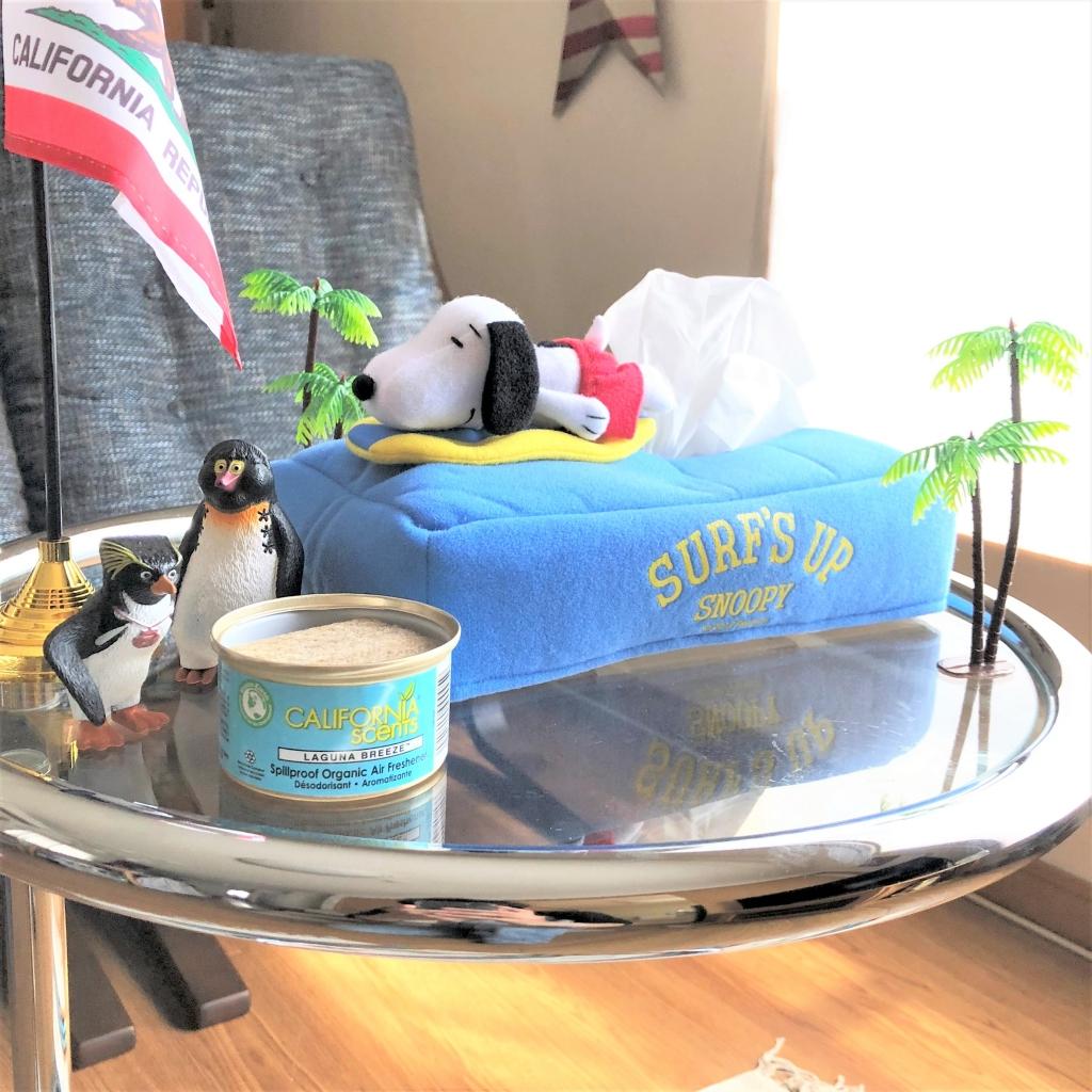 スヌーピーのティッシュケースとヤシの木のオブジェがテーブルの上に置かれている