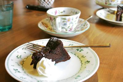 キッチンハートランド、テーブル風景。コーヒーカップとチョコレートケーキ