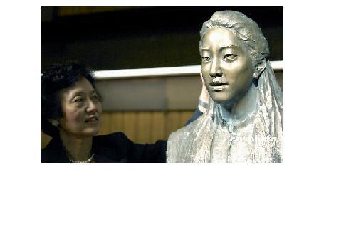 娘アイリスの像をなでる母ユンユン・チャン