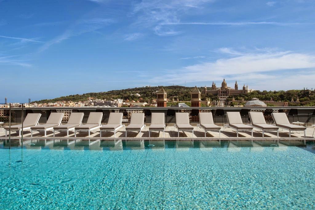Hotel Catalonia Plaza Booking.com プールの背景がモンジュイックの丘