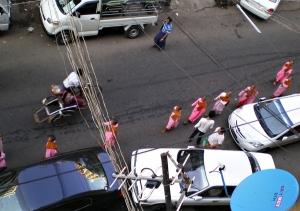 托鉢の尼さん達と街行く人。車の停め方がすごい。