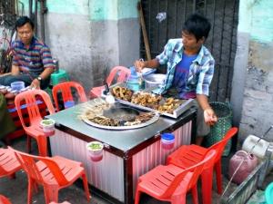 串揚げ屋さん。臓物を煮たものが串に刺してあり、真ん中の煮えている油に潜らせ、テーブルの縁にセットされているチリソースに浸けて食べる。