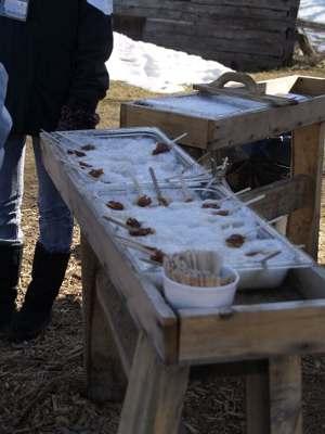 煮詰めてできたシロップ、雪の上にたらして棒でからめたら飴のできあがり