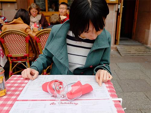 ストラスブールの広場のカフェでメニューを見る嫁さん