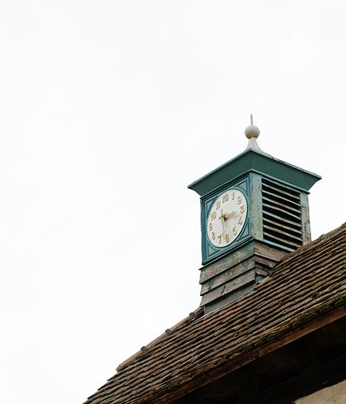 エコミュゼ/トラクターの並ぶ納屋の屋根の上の時計台