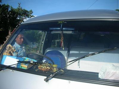車にお供えをするスハさん。