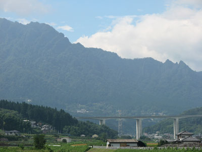 台風9号により増水した高田川から妙義山を背景に上信越自動車道の高架橋を望む