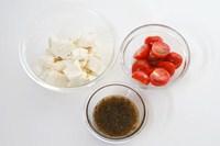 豆腐は手でちぎり、ミニトマトは半分に切り、ドレッシングを混ぜ合わせる。