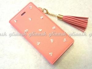 ピンクのタッセル付き手帳型iPhoneカバー