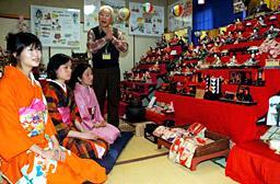 森館長(右)から雛人形の説明を受ける台湾の学生(手前の2人)