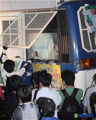 ハンマーでバスのガラスを割るデモ隊