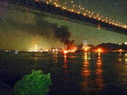 関門海峡を流されながら炎上する護衛艦「くらま」=27日午後8時9分、北九州市門司区、読者提供