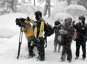 雪が絶え間なく降る中、上杉神社を取材する台湾・民視電視台の番組制作スタッフ=米沢市