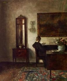 Stueinteriør med en sortklædt kvinde siddende med en bog