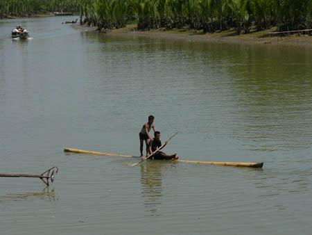 一本の巨竹を舟代わりに乗る村人たち