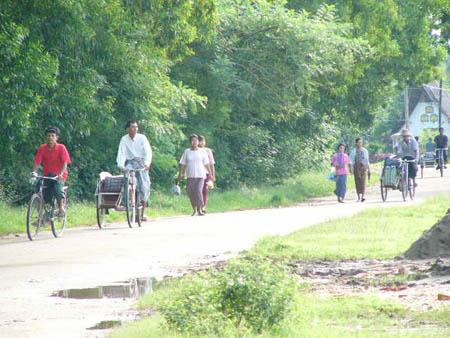 表の道路を通るサイカー(自転車タクシー)や歩行者