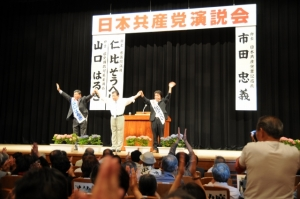鹿児島演説会で壇上から声援に応える市田書記局長、仁比そうへい、山口はるき選挙区候補