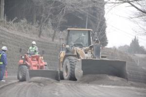 県道につもった灰を除去しているショベルカー