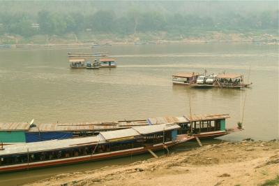 車を小船に乗せてメコン川を渡る人々