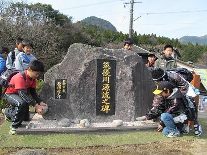 源流の碑に石を置く子ども達