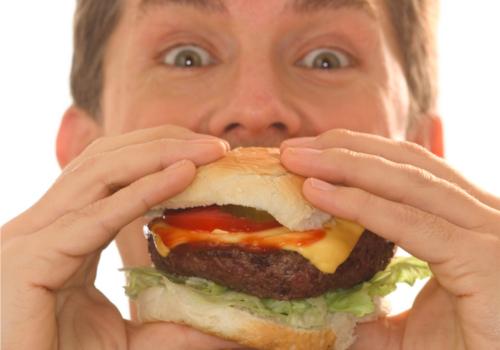 身体の噂・裏技・裏話_ハンバーガーを食べる男