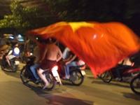 バイクで3人乗りで国旗を振りかざすベトナム人サポーター