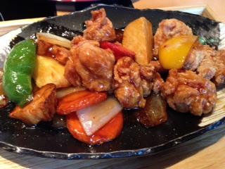 """『ごはん屋 御経塚 蔵八』の""""鶏肉と野菜の黒酢あん掛け膳""""は、柔らかいジューシーな鶏もも肉の唐揚げと彩りやゴロッとした食感を生かした野菜を特製の黒酢ダレであわせた一品だ。爽やかな黒酢の風味の効いた酸っぱ甘辛い味は、ご飯に良く合う。黒酢のコクと旨みが効く。"""