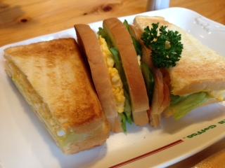 """『コメダ珈琲』の""""ミックストースト""""は、フワフワの山形食パンをトーストしてあり、サクサクと香ばしい食感が楽しめる。3枚のトーストされた食パンのフィリングは、刻んだゆで卵のマヨネーズ和え、レタス、キュウリ、ハム等で、写真からも、そのボリューム感が伝わる。"""