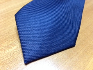 """『メーカーズシャツ鎌倉』で購入した""""50ozソリッドタイ""""は、高密度に織り上げているため、ドレープ感も程良く、艶を引き立て、 ネクタイを締めたときの心地よいフィット感をもたらしてくれる。また、肉厚ながらしなやかでシワになりにくく、ノットが緩まず美しい。"""