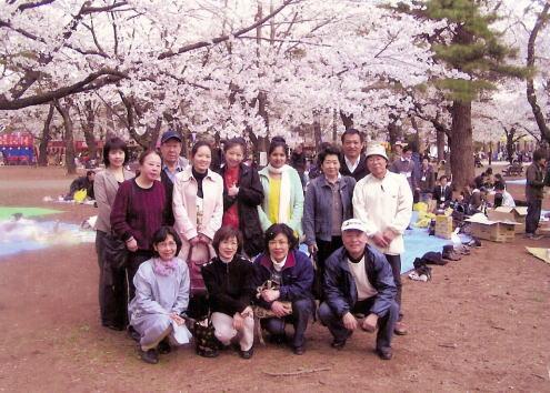 満開の桜を背景に全員で記念写真