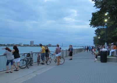 お気に入りアーティストを夕涼みしながら待つ人々。河の向こうはカナダ。