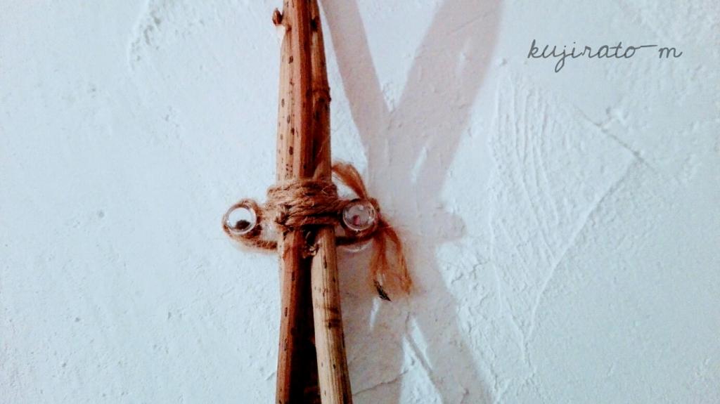 プッシュピンと麻ひもで、壁にドライフラワーを貼り付ける