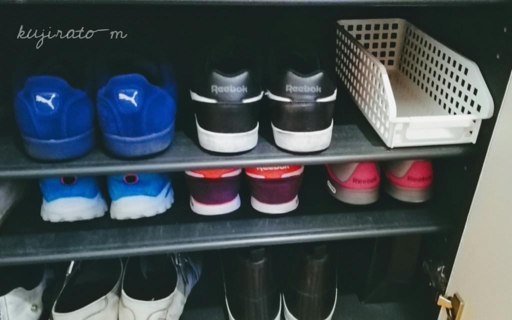 黒い靴箱の中で、白い収納ケースが浮く