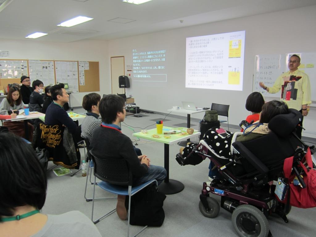 平田オリザ著「わかりあえないことから」を紹介しながら、「違いを活かすためには、人間としての共通性に目を向ける必要がある」と茂木さん 写真中央壁の白字画面は、PC要約筆記による情報保障