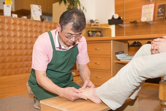 カウンセリング2。シューフィッターの仕事の一つ。足の裏の状態、足の骨格の状態、土踏まずなどの高さ、足の柔らかさ、タコやウオノメ、外反母趾、巻爪などが無いか、実際に触診します。