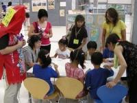地域通貨ゲームを体験する子どもを見守っています。