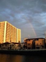 夕日に輝く建物と虹