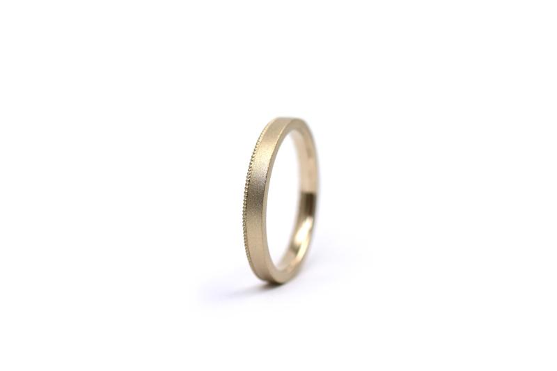 K18シャンパンゴールドによる洋彫りとミルグレインをお入れしたアシンメトリーデザインの結婚指輪です。