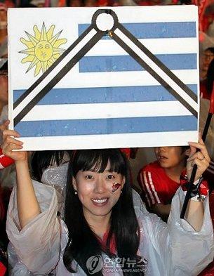 ウルグアイ国旗に喪章をつけて満面の笑顔の韓国人サポーター