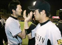 勝ち越し打の関本(右)とタッチする好救援の阪神・橋本健=神宮