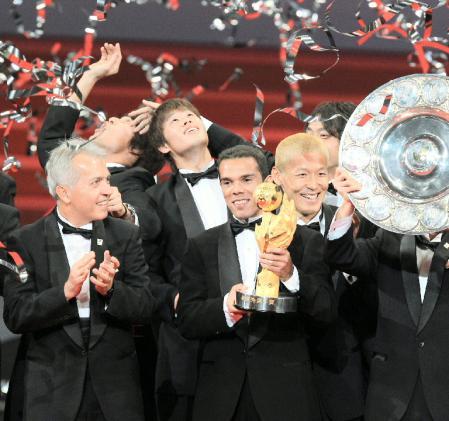 最優秀選手賞を受賞し柏イレブンと笑顔を見せるレアンドロ・ドミンゲス(後方・中はベストヤングプレーヤー賞の酒井宏樹)=横浜アリー
