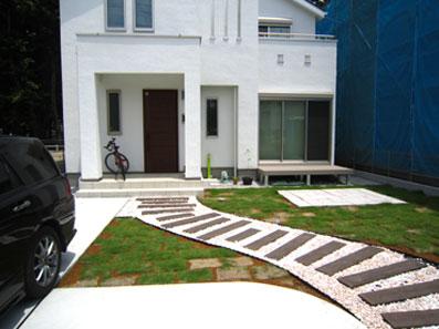 芝生のお庭にコンクリート製の枕木のアプローチと、自然石の敷石テラスも設置されています