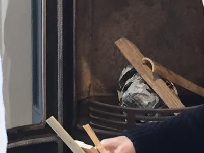 暖炉に紙を丸めてくべる
