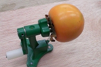 柿皮むき器実演1 金属製の串に柿を刺す