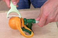 柿皮むき器実演3…ハンドルを回しピーラーを当てがって皮をむく