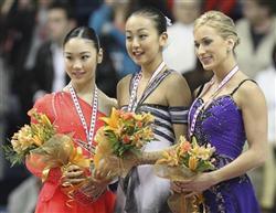 優勝した浅田真央(中央)、2位の中野友加里(左)、3位のジョアニー・ロチェット=11月3日、カナダ・ケベック(ロイター) <br />