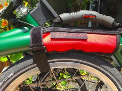 ブロンプトンのフレームに取り付けたオフヤーバイクのキャリングハンドル。面ファスナーを延ばしてタイヤに巻き付けている
