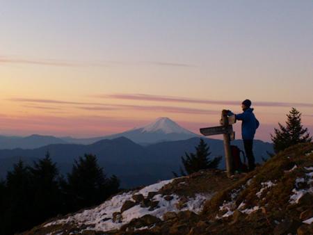 日の出を見つめる青年と富士山